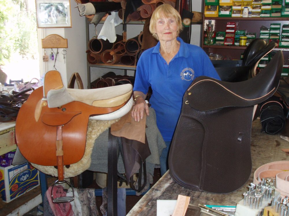 Wendy Tibold in her workshop with a tan and dark brown side saddle created from quality leather